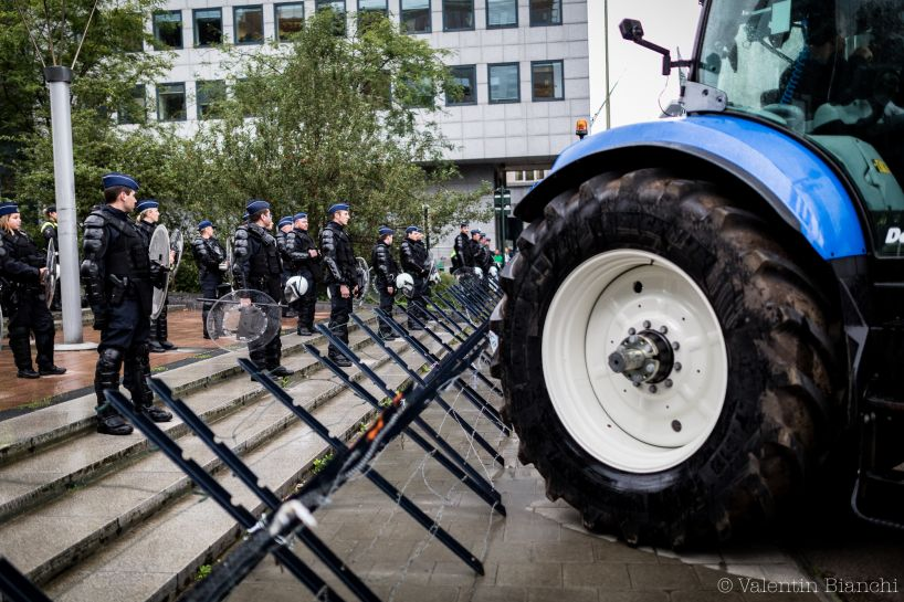 Police wearing riot gear and holding shields stand in front of a barricade as they protect european buildings in Brussels  during a protest by EU dairy farmers. September 7th, 2015. © Valentin Bianchi