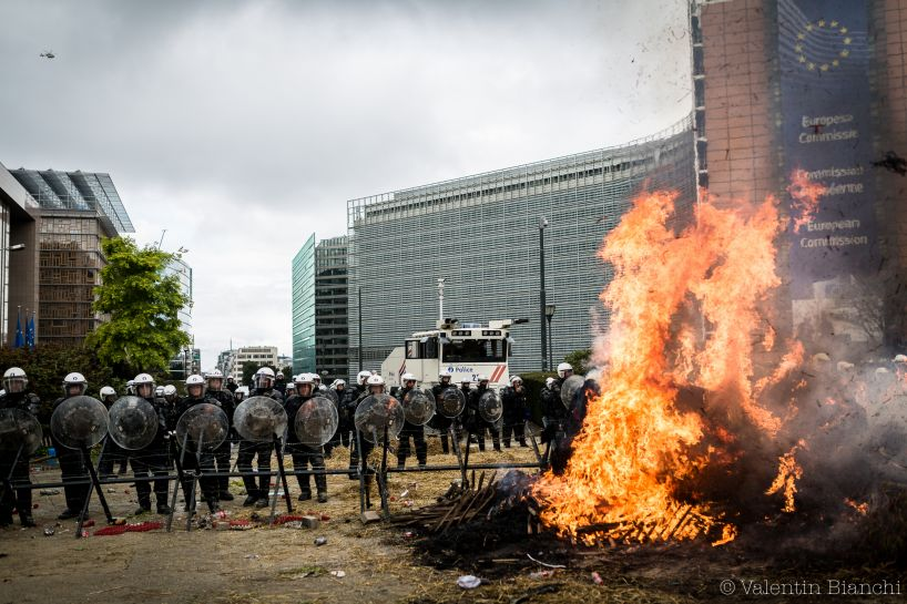 Police wearing riot gear and holding shields stand in front of a burning barricade as they protect the European Commission building in Brussels, Belgium during a protest by EU dairy farmers. September 7th, 2015. © Valentin Bianchi