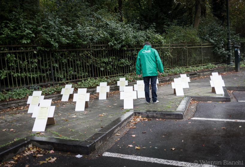 A demonstrator walks by white crosses representing migrant and refugee graves outside of an EU summit in Brussels on Thursday, Oct. 15, 2015. Demonstrators blocked roads around the summit, where leaders were meeting nearby, to protest against the Transatlantic Trade and Investment Partnership and European migration policies. (AP Photo/Valentin Bianchi)
