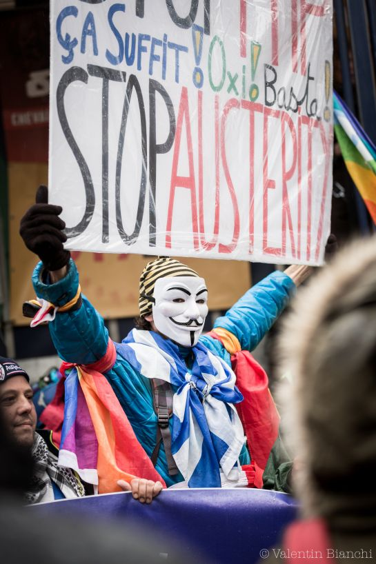 A demonstrator holds up a sign to protest against austerity measures outside of an EU summit in Brussels on Thursday, Oct. 15, 2015. Demonstrators blocked roads around the summit, where leaders were meeting nearby, to protest agains the Transatlantic Trade and Investment Partnership and European migration policies. (AP Photo/Valentin Bianchi)